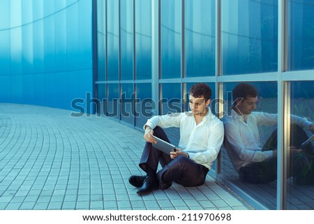 Portrait of young handsome successful business man near blue wall of business center holding digital tablet. Outdoor - stock photo