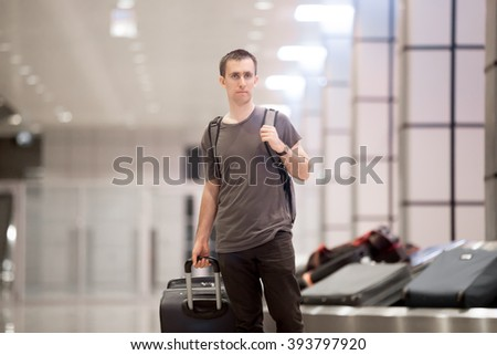 Portrait of young handsome traveller man in 20s leaving arrivals lounge of airport terminal building after collecting his baggage at conveyor belt - stock photo