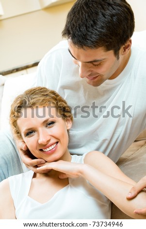 Portrait of young happy amorous couple at home