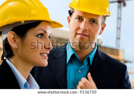 Portrait of young happy architects in front of construction site, building and crane. - stock photo