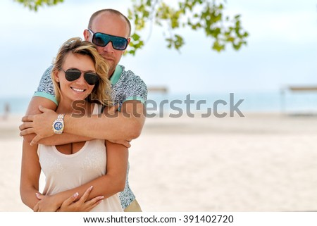 Portrait of young happy attractive couple standing at the sunny beach.