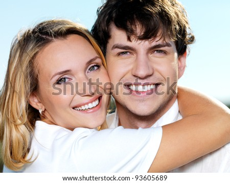 portrait of young happy beautiful couple on blue sky background