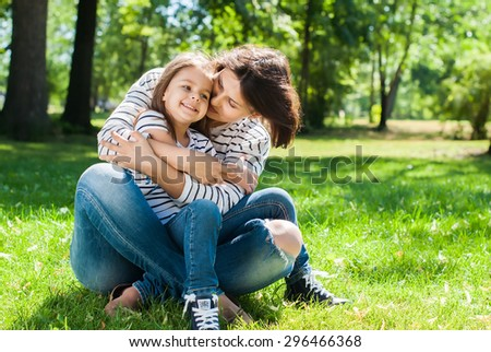 Portrait of Young Happy Beautiful Mother and Daughter. Embrace in Sunny Day on Meadow - stock photo