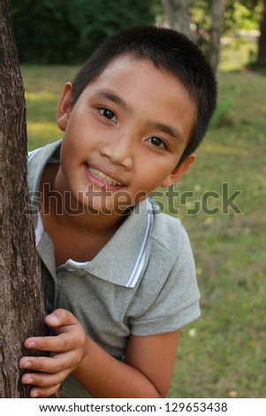 Portrait of young happy boy behind tree at park.
