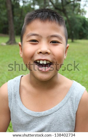 Portrait of young happy boy with green grass background. - stock photo
