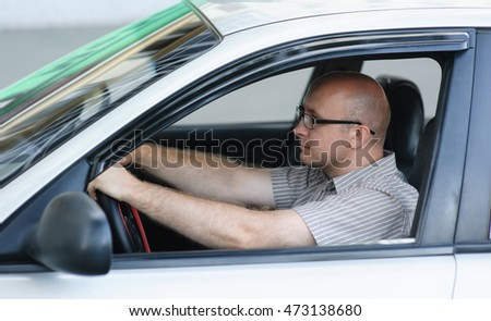 Portrait of young happy businessman in the car