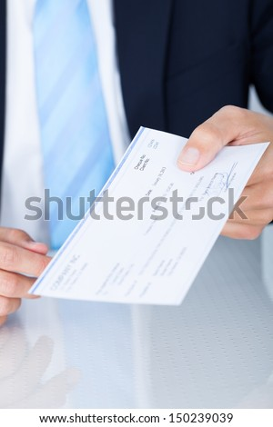 Portrait Of Young Happy Businessman Offering Cheque