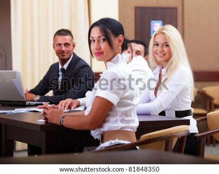 Portrait of young happy caucasian woman with her business partners on the background - stock photo