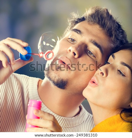Portrait of young happy couple blowing bubbles, outdoor - stock photo