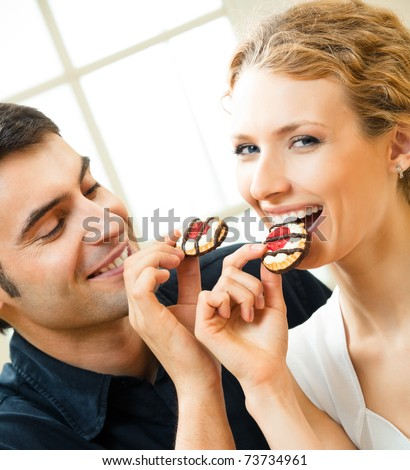 Portrait of young happy couple eating cakes at home