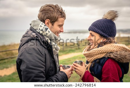 Portrait of young happy couple holding cups of hot beverage in a cold day with sea and dark cloudy sky on the background - stock photo