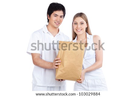 Portrait of young happy couple holding paper bag. - stock photo