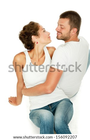 Portrait of young happy couple sitting on the floor, isolated on white background