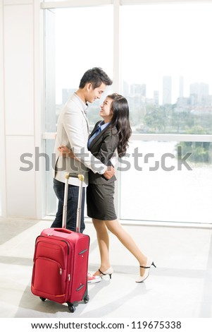 Portrait of young happy couple with baggage looking at one another in airport - stock photo