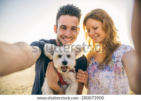 Portrait of young happy couple with dog taking a selfie - Lovers on a romantic date on the beach at sunset - stock photo