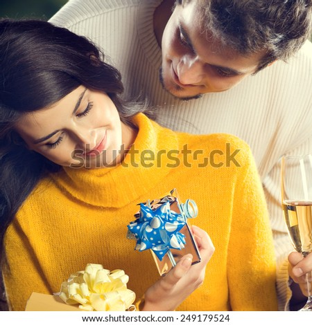 Portrait of young happy couple with gifts, outdoor - stock photo