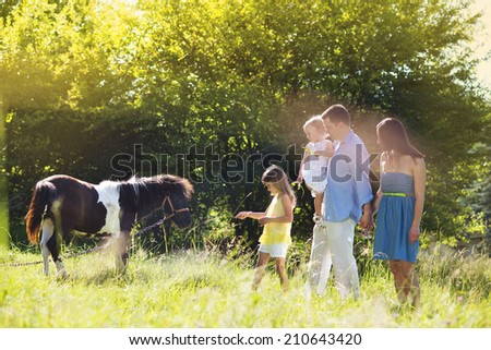 Portrait of young happy family at countryside outdoors, feeding pony - stock photo