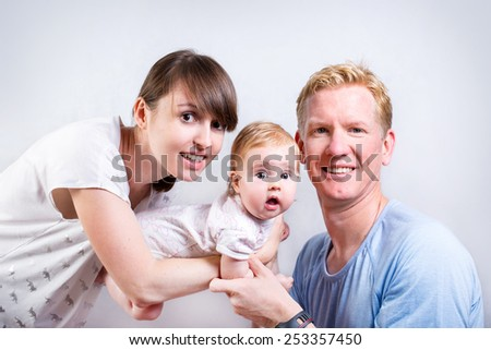 Portrait of young happy family. Cheerful parents with cute baby posing in the studio - stock photo