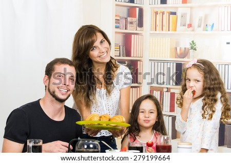 Portrait of young happy family eating breakfast - stock photo