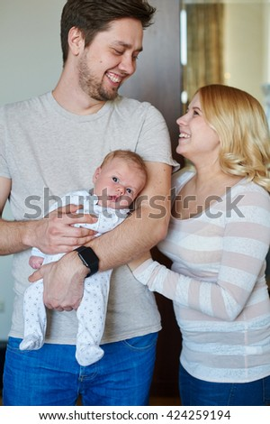 Portrait of young happy family with a baby - stock photo