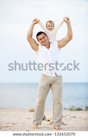 Portrait of young happy father playing with his child at the beach - stock photo
