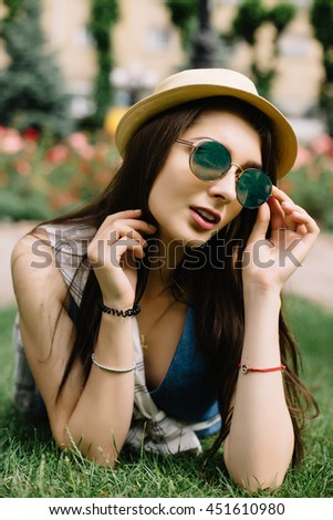 Portrait of young happy girl  with sunglasses and hat lying on grass in city park. Urban lifestyle concept. - stock photo