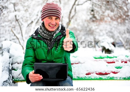 Portrait of young happy handsome man working on his laptop outdoor sitting on bench in winter park