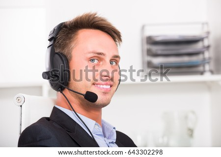 Portrait of young happy male operator with headset on answering at call center