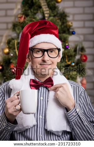 Portrait of young happy man in Santa hat with cup of tea - stock photo