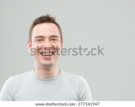 portrait of young happy man laughing and looking at camera