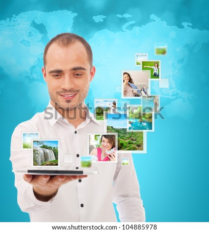 Portrait of young happy man sharing his photo and video files in social media resources using his modern tablet computer. Standing against World map - stock photo