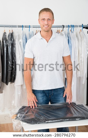 Portrait Of Young Happy Man Standing In Clothing Store - stock photo