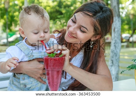 portrait of young happy mother with her baby son enjoying summer cocktail in outdoor street cafe - stock photo