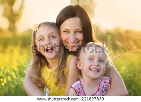 Portrait of young happy mother with her little daughters in sunny meadow