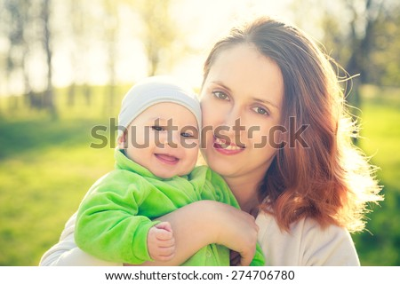 Portrait of Young Happy Mother with Her Smiling Baby in Park. Spring Nature Background. Family Love Concept. Toned Photo.  - stock photo