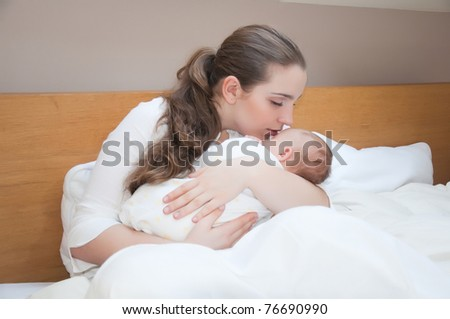 Portrait of young happy mother with newborn baby at home