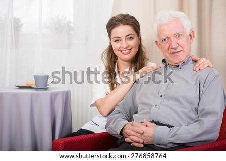 Portrait of young happy nurse and older nice male ward - stock photo