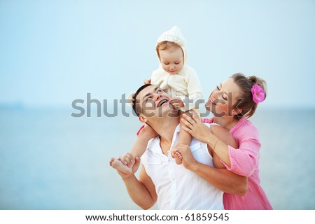 Portrait of young happy parents with child at the beach