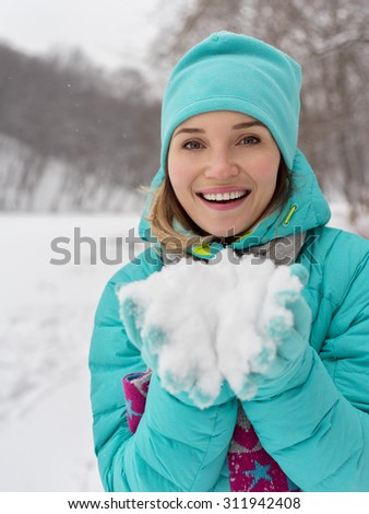Portrait of young happy pretty woman with snow in palms - stock photo