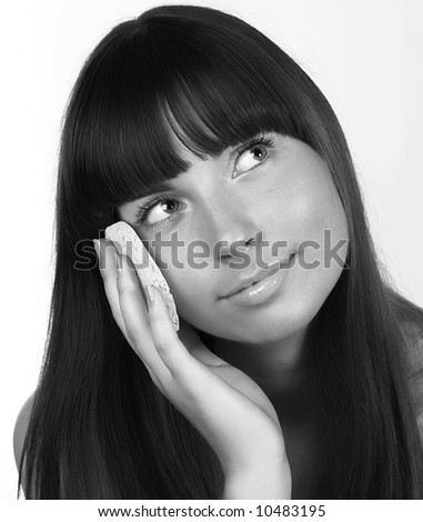 Portrait of young happy smiling beautiful woman applying creme - stock photo