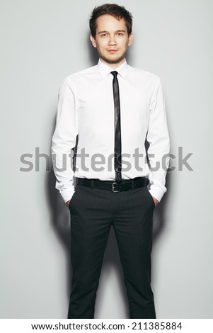Portrait of young happy smiling business man in trendy clothing with hands in pockets posing over gray background. Bristle on face and stylish haircut. Studio shot - stock photo