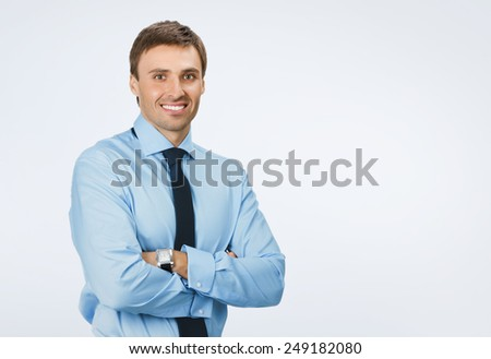 Portrait of young happy smiling business man, over grey background, with copyspace area for text or slogan - stock photo