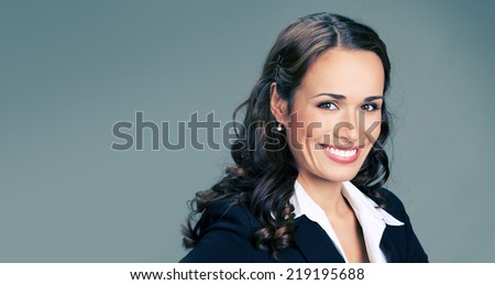 Portrait of young happy smiling business woman, over grey background, with copyspace - stock photo