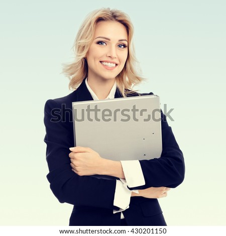 Portrait of young happy smiling businesswoman with grey folder, with blank copyspace area for slogan or text - stock photo