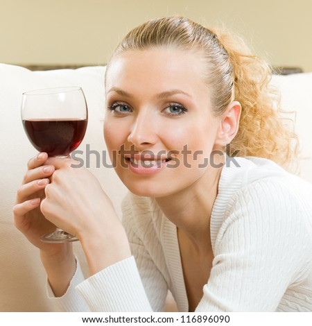 Portrait of young happy smiling cheerful beautiful blond woman with glass of red wine - stock photo