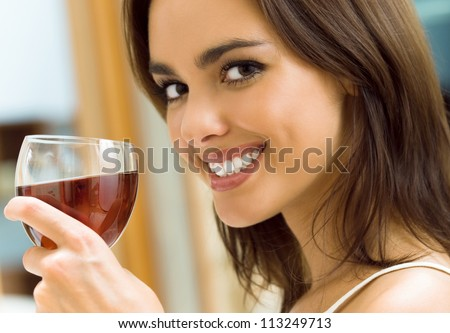 Portrait of young happy smiling cheerful beautiful woman with glass of red wine