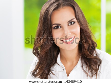 Portrait of young happy smiling cheerful business woman at office - stock photo