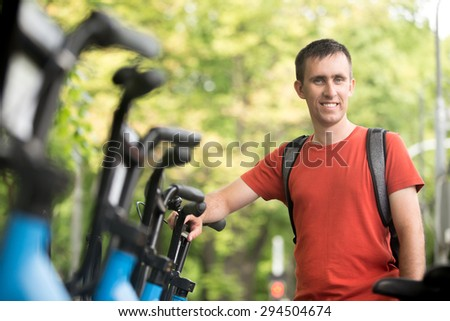 Portrait of young happy smiling man standing at rental city bikes parking lot, renting bicycle for ride - stock photo