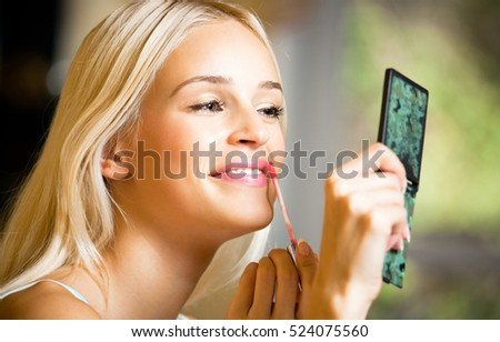 Portrait of young happy smiling woman applying lipstick at home. Beauty and fashion theme concept.