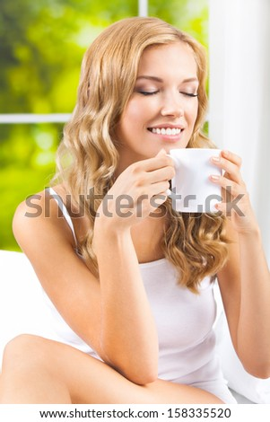 Portrait of young happy smiling woman drinking coffee or tea, at home - stock photo